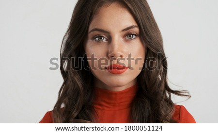 Portrait of gorgeous serious brunette girl with red lips intently looking in camera isolated