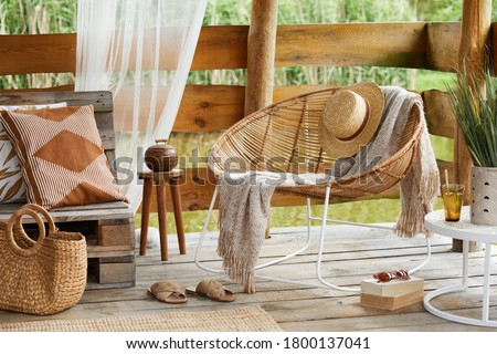 Interior design of  summer gazebo by the lake with stylish rattan armchair, coffee table, sofa, pillows, plaid and elegant accessories in modern decor. Summer vibes. Royalty-Free Stock Photo #1800137041