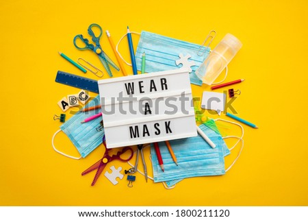 Wear a mask lightbox message with school equipment and covid masks