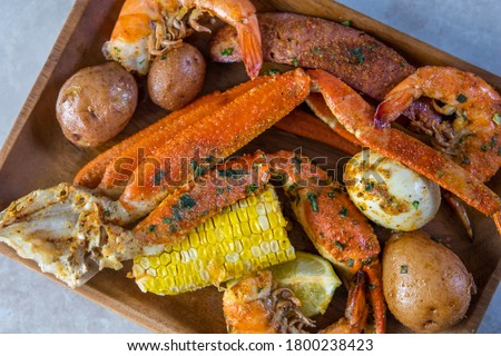 Platter of southern garlic crabs seafood boil with Alaskan crab legs, small new red potatoes, corn on the cob, and shrimp #1800238423