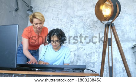 woman and boy playing together in studio on midi keyboard and laptop. Royalty-Free Stock Photo #1800238456