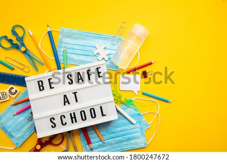 Be safe at school message with school equipment and covid masks