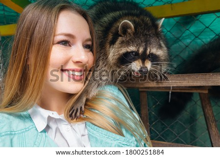Young girl plays and takes pictures with a raccoon
