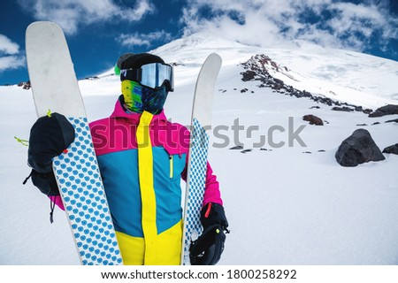 Portrait of a women skier in a multi-colored bright jacket in a ski mask with her face closed on a sunny day against the backdrop of snow-capped Caucasian mountains and clouds #1800258292