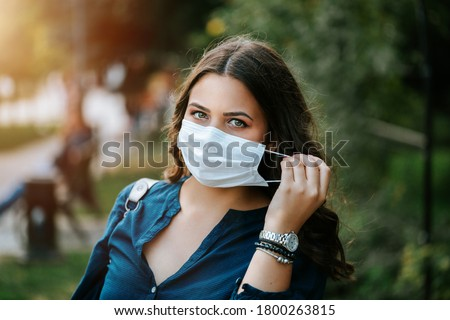 Young brunette beautiful women in city street or park weared with face mask that protect against the spread of corona virus disease or SARS-CoV-2. Social distancing during pandemic COVID 19. Royalty-Free Stock Photo #1800263815