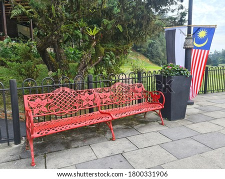 Malaysian flags with red metal chair garden look hanging at a Fraser's Hill, Pahang, Malaysia