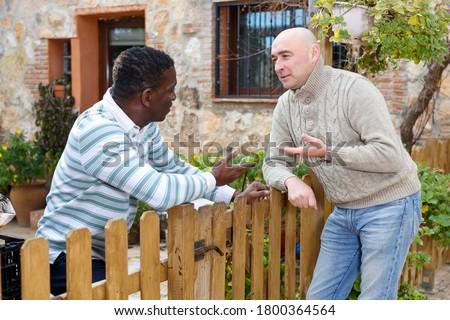Good neighbors talk on the border of their farms. High quality photo #1800364564