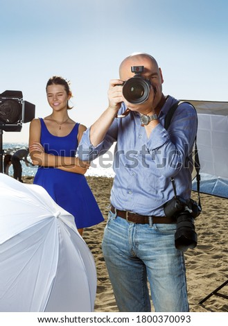 Male photographer with large professional camera looking into viewfinder and taking pictures on ocean coast