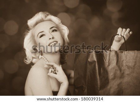 Pretty blond girl model like Marilyn Monroe with shopping bag on red background
