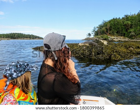 A mom and young daughter on a row boat taking a photo of a seal on a rock, while traveling in the Gulf islands, British Columbia, Canada
