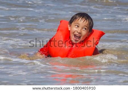 A happy young boy wearing a life vest is swimming in the ocean. #1800405910
