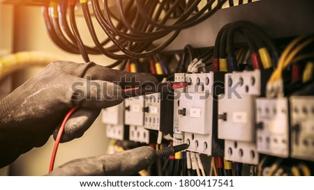 Electrical engineer using digital multi-meter measuring equipment to checking electric current voltage at circuit breaker and cable wiring system in main power distribution board. #1800417541
