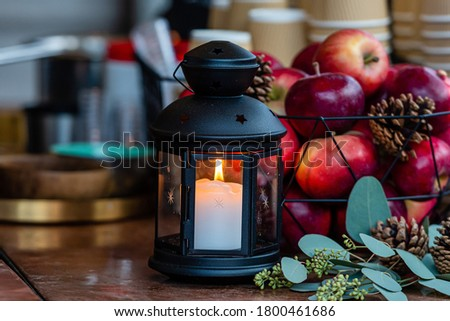Glowing candle lantern and basket of apples on the table in the Christmas Market in Riga, Latvia - image