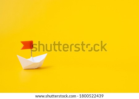 White paper boat with a red flag on a yellow background. Concept .