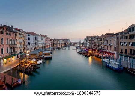 Grand Canal of Venice in a long daytime exposure. The artificial light from the restaurants and streets merges with the natural late afternoon light, giving a fantastic picture with the silky canal.