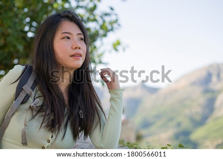 young happy and attractive Asian Japanese tourist woman hiking and enjoying beautiful mountain view during Summer holidays travel in travel and tourism concept