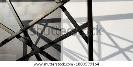 Black and shiny steel bars on the cement wall