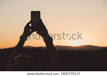 A man photographing sunset over the Madrid in Spain by a smartphone Royalty-Free Stock Photo #1800739273