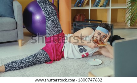 Retro stylish young man jerk eating pizza while doing leg exercises and watching training classes on laptop online. Fitness comedy. Sports and humor concept.
