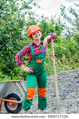 tired construction work. girl builder takes a shovel of rubble. hardworking youth. game of builder and construction. Outdoor activity concept. girl who is transporting rubble in a wheelbarrow. #1800757528