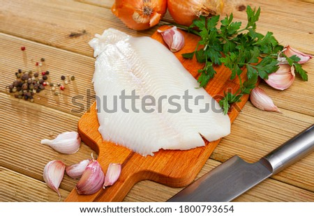 Fillet of raw halibut fish on wooden surface with garlic and greens