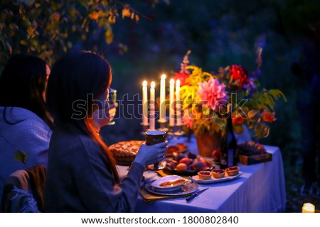 Autumn evening photo shoot: young woman with wine glass at romantic dinner in twilight nature outdoors. Table decoration - cake, figs, plates, candelabra with candles, fall flowers. Red dahlia bouquet