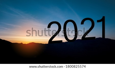 Happy New year 2021 letters on the mountain with sunset light, Silhouette of year 2021 with sunrise on mountain for New year success, Starting of New year concept.