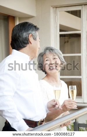 Senior Japanese couple drinking champagne on the balcony #180088127