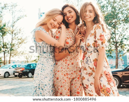 Three young beautiful smiling hipster girls in trendy summer sundress.Sexy carefree women posing on the street background. Positive models having fun and hugging.Walking after shopping