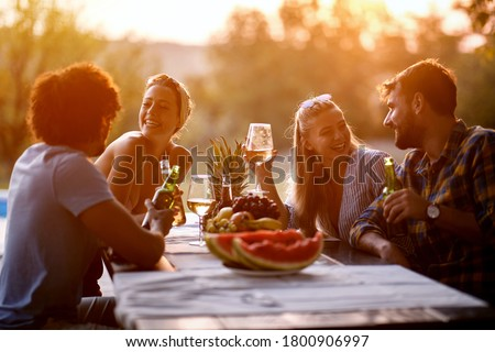 Young friends having fun outdoor, talking and laughing enjoying at evening. Royalty-Free Stock Photo #1800906997