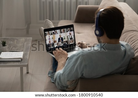 Rear view of male employee in headphones sit on couch at home office talk speak on video call on laptop with diverse colleagues, man have webcam digital virtual conference with coworkers on computer #1800910540