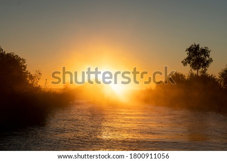 Sunset sky background. Gold sunset sky with evening sky clouds over the lake with fog.Crystal clear water texture. Small waves with water reflection Royalty-Free Stock Photo #1800911056