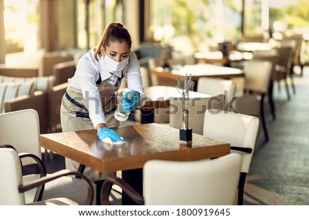 Young waitress disinfecting tables while wearing protective face mask ad gloves due to coronavirus epidemic.  Royalty-Free Stock Photo #1800919645