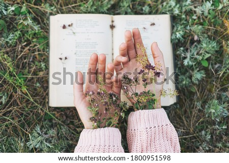 Women's hands with wild flowers on open book on the grass, love to read, slow living Royalty-Free Stock Photo #1800951598