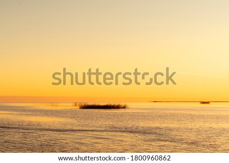 Sunset sky background. Gold sunset sky with evening sky clouds over the lake with fog.Crystal clear water texture. Small waves with water reflection Royalty-Free Stock Photo #1800960862