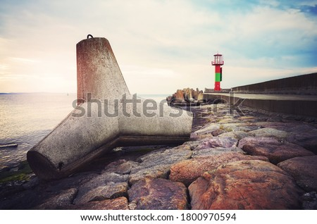 Concrete tetrapod breakwater on a pier in Swinoujscie at sunset, color toned picture, Poland. Royalty-Free Stock Photo #1800970594