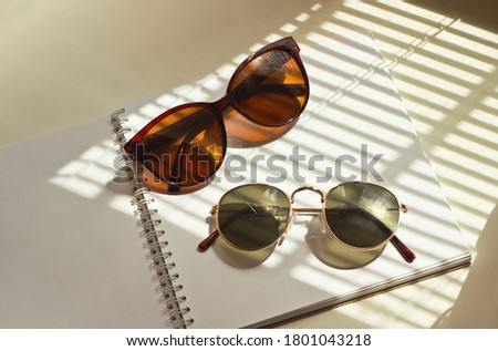 A pair of sunglasses lies on an open notebook in the rays of sunlight Royalty-Free Stock Photo #1801043218