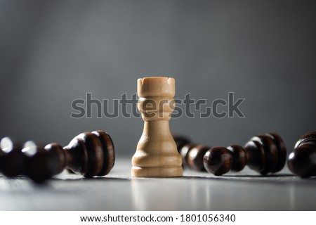 Resilience, perseverance, immunity and victory concept. Rook standing among fallen pawns. Royalty-Free Stock Photo #1801056340
