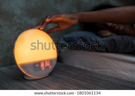 Black female lying in bed and turning off digital alarm clock after awakening early in morning in dark room #1801061134