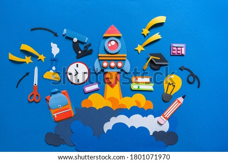 Rocket takes off paper craft. Back to school. Copy space. Blue background. Education concept
