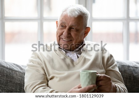Happy older retired man relaxing on comfortable sofa with cup of coffee tea, enjoying peaceful morning time alone in living room, visualizing future, meditating or recollecting good memories indoors.