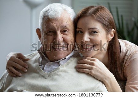 Head shot close up portrait of affectionate grown up daughter embracing shoulders of happy old mature retired father, showing love and care, posing for family photo, enjoying sweet tender moment.