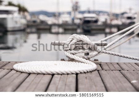 Nautical mooring line rope on the jetty. Curled mooring line. Royalty-Free Stock Photo #1801169515
