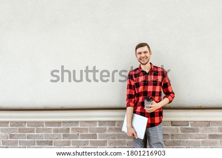 Young happy man freelancer is standing near a brick wall and holding a coffee and a laptop in his hands. Working everywhere concept. Copy space for text