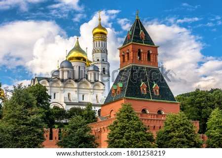Moscow Kremlin close-up in summer, Russia. It is top tourist attraction of Moscow. Old tower of famous Moscow Kremlin and ancient cathedral behind it. Medieval buildings in Moscow city center. #1801258219