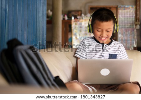 Online remote learning, distance education and homeschooling concepts. School kid Asian preteen boy in headphone using laptop computer on couch in rustic rural home during COVID-19 pandemic. Royalty-Free Stock Photo #1801343827