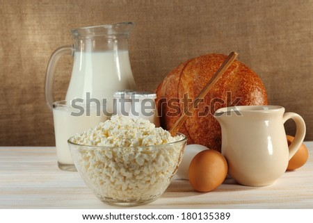 Tasty dairy products on wooden table, on sacking background #180135389