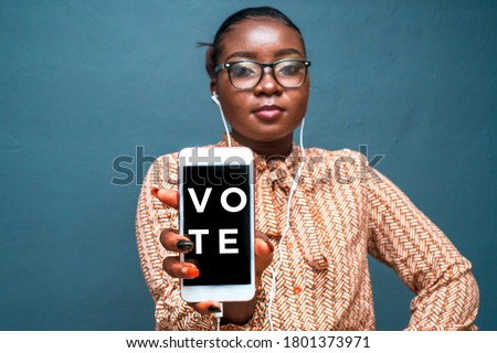 African woman holding a smartphone with vote on screen,main focus on fingers holding phone
