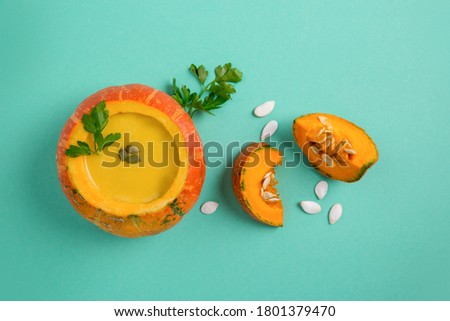 Pumpkin puree soup in pumpkin on colored paper background. Healthy eating. Pumpkin, pumpkin seeds