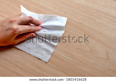 Alcohol clean pad wiping and cleaning wooden table for disinfect virus bacteria, prevent from epidemic of disease during the corona virus outbreak. Royalty-Free Stock Photo #1801416628